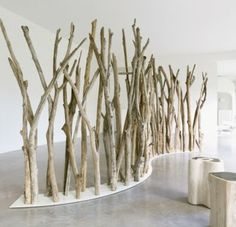 Natural Tree Branch Divider: Creation of Natsiq Outdoor, it features tree branches attached to a lacquered stainless steel base.