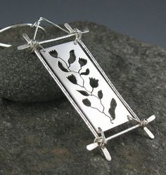 Sterling Silver Botanical Pendant Necklace, Handmade The centerpiece of this dramatic sterling silver pendant is a delicate strand of flowers, which I cut out carefully using a jewelers saw. This center rectangle is suspended in a frame made of hammered, textured wire. The