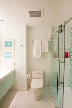 Keeping surfaces and countertops clear of toiletries and trinkets enhances the crisp, clean design of this small bathroom. A sliding glass door for the shower is an ingenious way to save space.