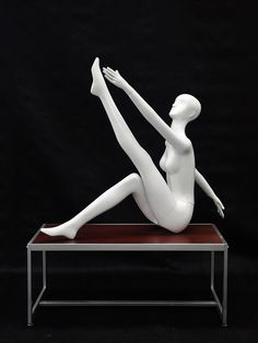 "Gabriella 7 is an abstract female mannequin made of white glossy fiberglass. She is in a ""sitting with one leg stretched to the ceiling"" pose. She would look great wearing dance and/or yoga apparel or"