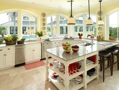 yellow kitchen, white cabinets, lots of natural light, large arched windows, no wall cabinets, red glasses