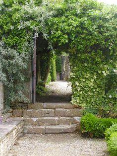 Natuurstenen trap geflankeerd door lagen heg en gespiegeld aan de andere zijde lage muurtje.  Owlpen Manor