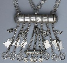 Detail of a large and extremely long Kurdish necklace in low silver or alloy with a double quatrefoil chain. The large cylinder amulet opens, and another small one hangs underneath with many botehs, flower/hand shapes, and circular symbols that I don't know the meaning of. The work on this is very nice, every single link is soldered including the hundreds of links on the quatrefoil chain. Perhaps from Iraqi Kurdistan?  Confirmation would be appreciated.