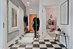 druciane ażurowe lampy, białe rzeźbione lustro na szarej ścianie,biało-czarna szachownica z płytek na podłodze,metalowy wieszak stojak