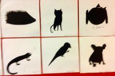 Sylwetki zwierząt z wycięte z czarnego papieru, przygotowane na podstawie rysunku konturowego.