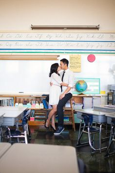 the couple took their engagement photos in the classroom where they met in third grade :)   best idea ever.