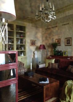 Living room. Contrasting colors. Wall is olive color and furniture is burgundy color. Chests with mirror inserts