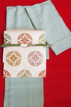 淡いグレーブルーの色無地着物に白地の帯とその柄の中から一色選び、帯揚げに持ってきた粋なコーディネート。
