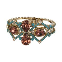 "Exotic Dream Small Cuff € 330,- The Exotic Dream Cuff was designed for the Spring Summer Rodrigo Otazu Couture Collection, named Everlasting, inspired by Jewelry from Exotic cultures. An unique and exotic colouring, using the turquoise blue and ""blush rose"" crystals from Swarovski, this cuff is perfect for a warm summer night or an exotic beach party. The turquoise blue and ""blush rose"" coloured cuff is finished by the 14k antique gold plated band. Handmade in Europe with care."