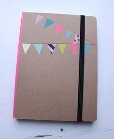 Bambus notesbog, tusch og maskingtape. Lav vimplen en bue fra øverste højre hjørne og ned/ind mod ryggen i stedet.