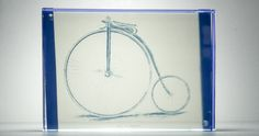 """This image is of a Penny Farthing frozen in time and space with a magnetic frame and cyanotype print.    Penny-farthing- term used to describe a type of bicycle with a large front wheel and a much smaller rear wheel that was popular after the boneshaker, until the development of the safety bicycle, in the 1880s. They were the first machines to be called """"bicycles"""""""