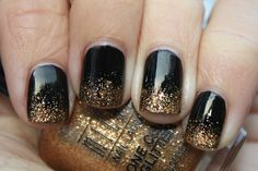 Black nails with gold glitter gradient tips.