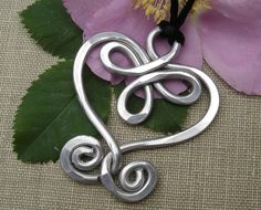 This Celtic heart pendant is A LOT lighter than it looks because it is made from wonderful versatile aluminum. The pendant measures about 2 1/4-2 1/2 (5.7-6.4cm) long and about 1 5/8-1 3/4 (4.1-4.4cm) across the widest part.  It hangs on a simple 32 (81.28 cm) black satin cord that can be tied to any length.  Looks great short or long.  If youd prefer a cord or chain with a clasp check out the Cords and Chains section of our shop to see all our cords and chains with clasps options available…