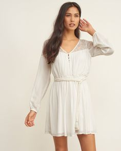 A pretty peasant dress with lace panel detailing, featuring a neckline with button details, a waist with a braided tassel belt and cinched sleeves, Classic Fit, Imported