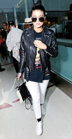 Kylie Jenner in a leather moto jacket + graphic tee + trousers + sneakers.