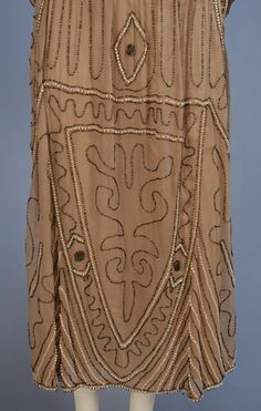 Beaded Dress 1922 Chandler & Co  Taupe silk dress with tabard top over short kimono sleeves. Low waist with gathered skirt and self sash. Decorated in an abstract pattern of large milky white beads and smaller charcoal glass beads. The dress has a silk charmeuse attached underdress. Detail 4 Private collection