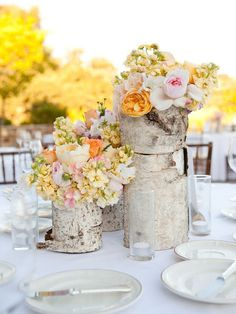 centerpieces: flowers in wooden logs <3 [from Once Upon a Misadventure]