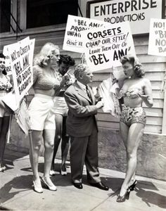 """Actresses appearing in the period drama The Private Affairs of Bel Ami, led by Marie Wilson (right), humorously protest to director Albert Lewin against the use of corsets"""