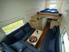 """The sleeping loft on the top level, the built-in sectional on the mid-level, and the kitchen and home office on the """"ground"""" level...with a path to the cab. Big thanks to AT reader Maren who sent us these awesome photos of a guy who lives out of...garbage truck? Correction: A highly modified garbage truck. This small space is nicer than some apartments we've seen! Hardwood floors...custom kitchen (with perfect storage!)...and a comfortable built-in sectional. See all the photos after the…"""