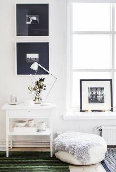 Ystävän ottamat valokuvat on kehystetty olohuoneen seinälle. Valkoiseksi maalattu sivupöytä on ostettu kirpputorilta. Marokkolainen nahkarahi on kierrätyskeskuksesta. Ikkunalaudalla on Jouni Haralan valokuvateos.