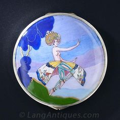 Art Deco Enamel Compact. An exotic nubile beauty is decked out in almost full regalia in this surreal Art Deco compact crafted in silver, metal and colorful enamel. 1920s.