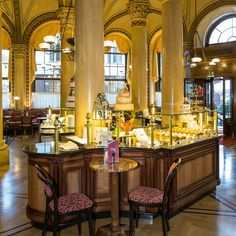 traditional with hanging red velvet drapes and upholstered chairs, inviting display cabinets of delectable sweet temptations and crystal chandeliers. Starbucks who? This is the cafe Central Cafe Central, Coffee Kombucha, Sacher, Coffee Coupons, Velvet Drapes, Road Trip Europe, Vintage Bar, Old City, Upholstered Chairs