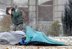 Jeff Dana, one of the Occupy Missoula campers, braces against the wind and snow Friday afternoon while securing his flattened tent on the front lawn of the Missoula County Courthouse during the worst of the blizzard. KURT WILSON/Missoulian