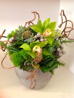 Designed for West Elm. Green cymbidium orchids, aspidistra leaves, green dianthus, scabiosa pods, silver brunia, succulents, rosemary, kiwi vine and a touch of moss. Designed by Green Bouquet Floral Design www.greenbouquetfloraldesign.com