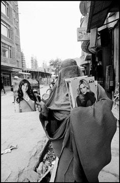Woman in a burqa selling glamour magazines. Kabul, Afghanistan, 2010 by Larry Towell (Canadian; b1953)