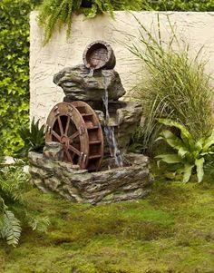 dekorative Wassermühle und Findlinge im Garten