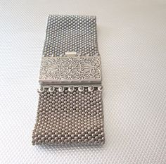 A silver beaded cuff made of seed beads and an intricate box clasp. This bracelet is both beautiful and a little edgy at the same time. It is a statement bracelet that will go with everything from a motorcycle jacket and jeans to a little black dress. Be bold and unique. Show your individuality with this one of a kind bracelet. It fits a 7 1/2 wrist. It is 1 1/2 wide. Treat yourself