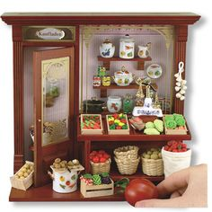 The Grocers Shop Shadow Box from Reutter Porcelain with the word Kaufladen over the door which means shop in German is open for business. The shop store front has everything a dollhouse patron would w