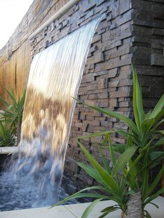 How To Build A Waterfall Wall for Outdoor and Indoor Decoration : Astonishing House Garden Decoration With Beautiful Waterfall In The Brick Fence Fall Into Big Pool Mixed With Several Flower Plant Beside It
