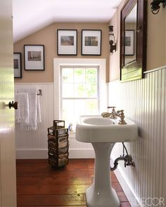 Photographs by Marcy Robinson and a pair of antique sconces, formerly railroad lanterns, in a bathroom.