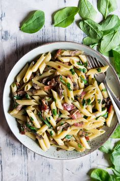 Easy mushroom spinach pasta made with smoked streaky bacon, crimini mushrooms (chestnut mushrooms), penne pasta and a splash of cream. Easy 10 minute recipe!