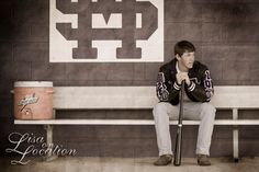 Baseball player poses on the bench with for his senior photo