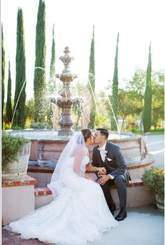 The bride and groom in front of a fountain and cypress trees during their winery wedding. The landscaping at Mount Palomar Winery in Temecula wine country was the perfect backdrop for their vineyard wedding! #mountpalomarwinery