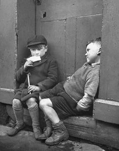 Two boys sitting on a doorstep. Photograph by Nat Farbman. Bolton, United Kingdom, April 1947.