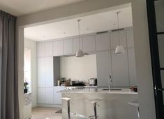 Large fitted kitchen finished in matte grey lacquer. Kitchen counters made of white Corian
