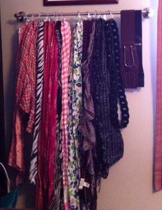 Belts and Scarves hung from towel rack and shower curtain hooks