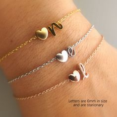 Dainty minimalist heart and initial bracelet in 16k gold, silver and rose gold plating. Initials are tiny CURSIVE , lowercase 6mm in size and are STATIONARY. This listing is for ONE bracelet only Standard size is 7 inches and comes with one 1,5 inch extension If you are unsure of the size, measure wrist then add one inch to find exact size . Then state in the notes to seller your measurement. CARE: This bracelet is delicate, please handle with care. Avoid contact with water, pools…