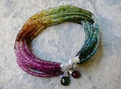 L'Acrobaleno: Twelve strands of multicolored tourmaline that make a rainbow wrapped around your wrist. The lustre of these gems is breathtaking. Photos cannot do it justice. Blue, green, orange, pink, magenta...just like a rainbow. The piece is finished with two colors of wire wrapped, tourmal