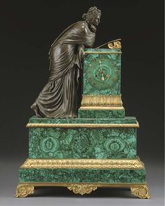 A FRENCH GILT BRONZE AND MALACHITE VENEERED MANTEL CLOCK  MID 19TH CENTURY  The stepped case flanked by figure of a muse, the twin barrel movement with countwheel strike on bell, backplate stamped 'BAULLIER & FILS, PARIS, 1121'  25½in. (64.7cm.) high; 18in. (45.6cm.) wide; 6in. (15.3cm.) deep