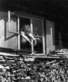 Two kids at the window of the chalet in April, 1946, at Tyrol, by Robert Doisneau