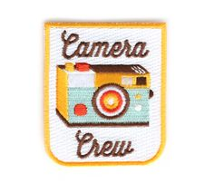 """Do you like cameras? Do you own a camera? Do you think technology is just the coolest thing?  Then you're in the Camera Crew!! Snag this patch and show the world that you know how to click that button.  Iron-on backing. Measures 2.5"""" tall x 2.125"""" wide"""