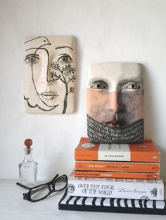 Two ceramic faces. One inspired by Picasso, the other by tribal tattoos.