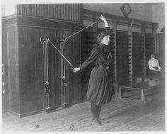 Female student exercising with a wall-mounted device using ropes and pulleys, Western High School, Washington, D.C. by Johnston, Frances Benjamin [1899?]