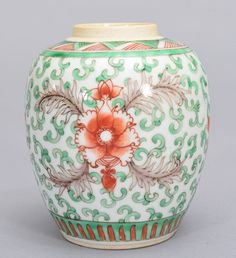 A WUCAI JAR, Period Of KangXi. The jar is wide globular-shaped and the exterior is decorated with two large flower blossoms surrounded by numerous green ruyi clouds. On the base of the jar, there is a double blue ring design. 5 1/16 in. tall, 4 7/16 in. diameter.