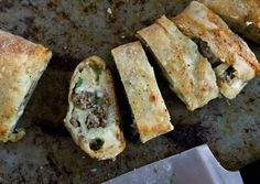 Stretch 1 pound store-bought pizza dough to fit a standard-sized rimmed baking sheet. Scatter cubes of mozzarella cheese, cooked ground beef, caramelized onions and crumbled blue cheese evenly across the dough, leaving a 1 1/2-inch border. Gently press the toppings into the dough and, beginning at a long end, loosely roll up the dough, pinching the edges together to seal. Bake in a 425° oven until puffed and golden brown, about 20 minutes.