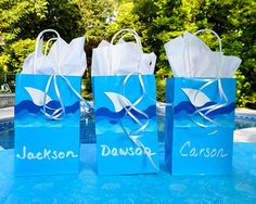 Shark birthday party ideas for party bags and favors.  Use a wave bulletin border and white foam paper for the fin.  I love the liquid chalk markers for writing names - if you goof up you can wipe it off and re-do.